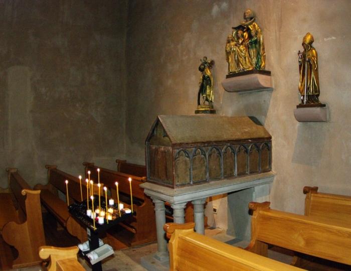 Над саркофагом расположены скульптуры (слева-направо): св. мученика Христофора (250), свв. мучениц Веры, Надежды, Любови и Софии, епископа Ремигия, основателя аббатства.